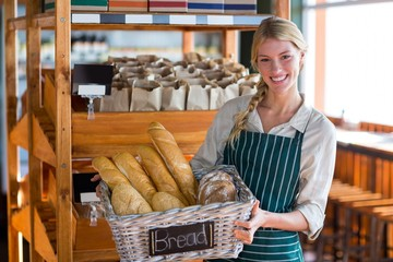 Smiling female staff holding basket of bread at bread counter