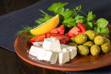 feta cheese, tomatoes, olives and herbs in a clay plate