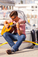Young guitarist sitting on pier.