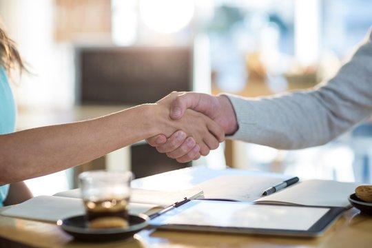 Friends shaking hands in café
