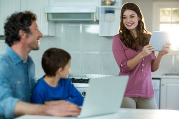 Family using digital tablet and laptop