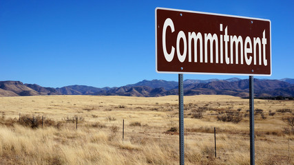 Commitment brown road sign