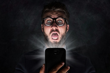 Mann mit Smartphone erhält entsetzliche Nachricht