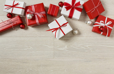 Christmas gifts presents on rustic wood background. Red and white wrapped gift boxes with ribbon bows.