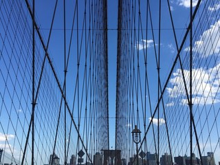 the symmetry of Brooklyn bridge cable and buildings with blue sky, New York