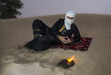 Tuareg man in a desert making fire