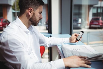 Man using mobile phone while reading newspaper
