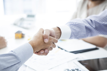 Businessmen and customers who are shaking hands in the company
