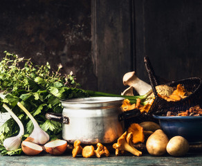 Cooking pot, forest mushrooms and cooking ingredients for soup or stew on dark rustic kitchen table at wooden background, side view, border