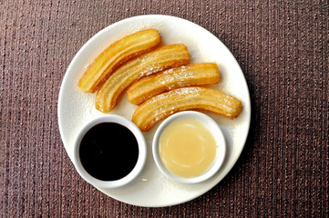 Homemade Spanish churros with dark and white chocolate dipping sauce