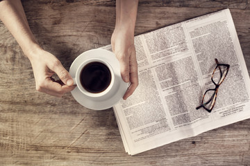 Young woman reading newspaper and holding coffee cup