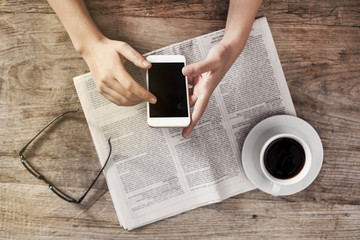 Young woman reading newspaper and holding phone