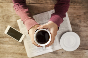 Young woman reading newspaper and holding coffee
