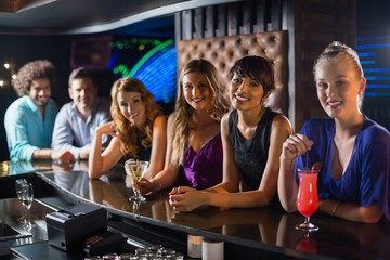 Smiling friends standing together at bar counter