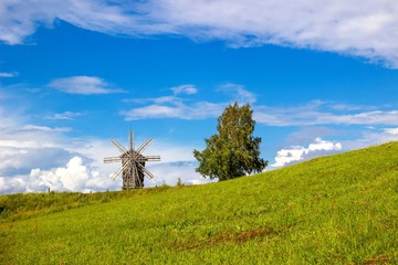 Rural landscape. Traditional wooden windmill on green hill. Kizhi Island. Karelia, Russia. UNESCO heritage landmark