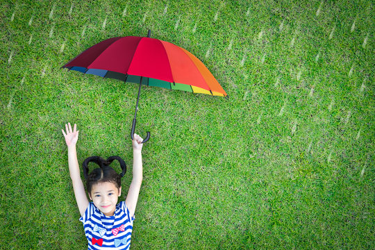 Happy asian girl kid raising hand lying on natural green grass lawn eco bio background holding rainbow umbrella protect in rainy weather day: Insurance protection safety health care concept