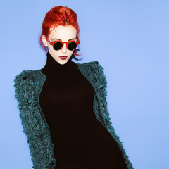 Glamorous lady with red hair and style sunglasses trend.
