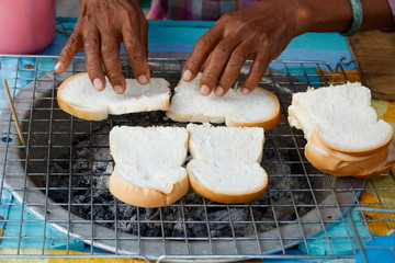 Grilling bread with stove street food in Thailand topping with jam or butter and sugar, selling on two pieces five baht thai