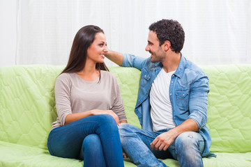 Happy couple sitting on sofa at their home and talking.