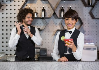 Two bartenders preparing cocktail and serving
