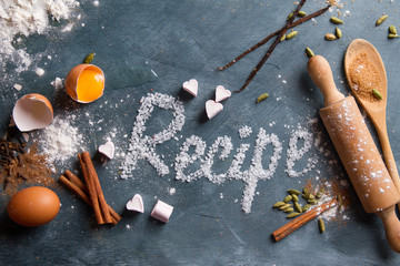 Wooden kitchen utensils with spices and recipe word