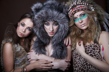 Portrait of beautiful three young girls of America in the fur and Indian outfit