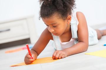 Preschool child girl drawing on the floor