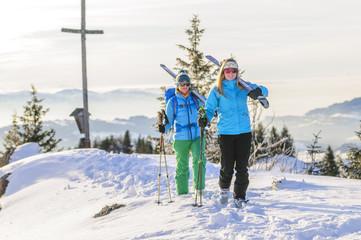 zwei Wintersportlerinnen mit Skiern am Gipfel