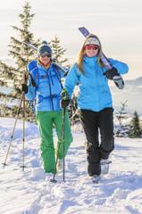 Zwei Skifahrerinnen gehen mit Skiern auf den Schultern bergauf