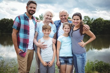 Happy multi-generation family standing near a river