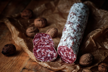 Italian salami with walnuts on craft paper on rustic  wooden background.