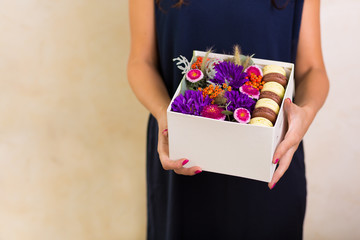 Woman holding a box with flowers and macaroon cookies