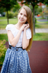 Portrait of a beautiful young girl in the Park skirt blouse nature fashion style