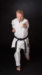 Fighter performing karate stance on black background