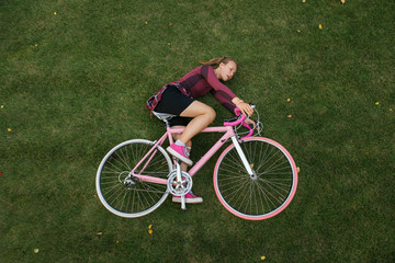 Top view of woman with bicycle on the grass