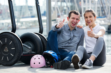 Couple sitting near segways at sea front
