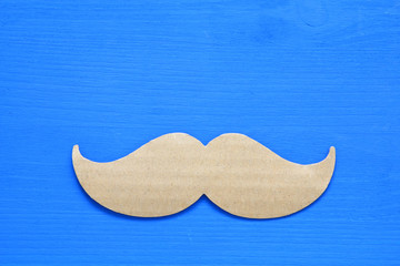 Blue wooden background and paper mustache