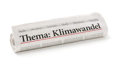 Zeitungsrolle mit der Überschrift Klimawandel