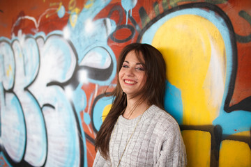 trendy beautiful long haired young model with piercing smiling on graffiti background