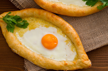 Khachapuri with eggs close-up on sacking