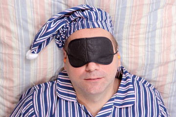 man sleeping with a mask on eyes