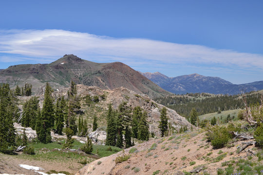 View from the trail to Winnemucca Lake from High Top Lake in the summer,  featuring mostly melted snow packs and a cloud stripe over the mountains