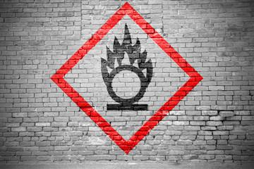 Ziegelsteinmauer mit GHS-Piktogramm Brandfördernd Graffiti