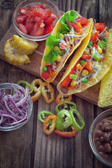 Mexican corn tortilla tacos with vegetables on wooden background