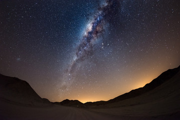 Starry sky and Milky Way arc, with details of its colorful core, outstandingly bright, captured from the Namib desert in Namibia, Africa. The Small Magellanic Cloud on the left hand side.