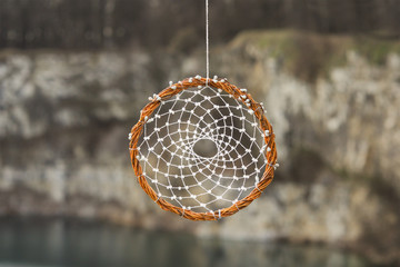 Handmade dream catcher on background of rocks and lake