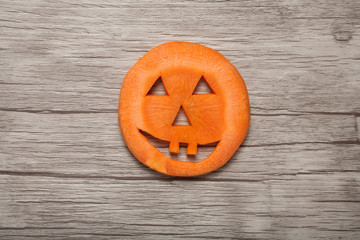 Halloween pumpkin made of carrot on wooden background