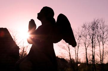 Engelfigur im Gegenlicht am Abend auf dem Friedhof
