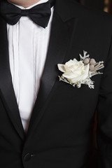 White and grey boutonniere on black suit of the groom