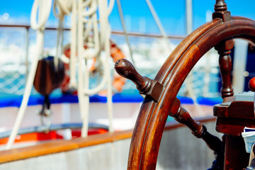 Closeup view on steering wheel of the ship, background outdoors